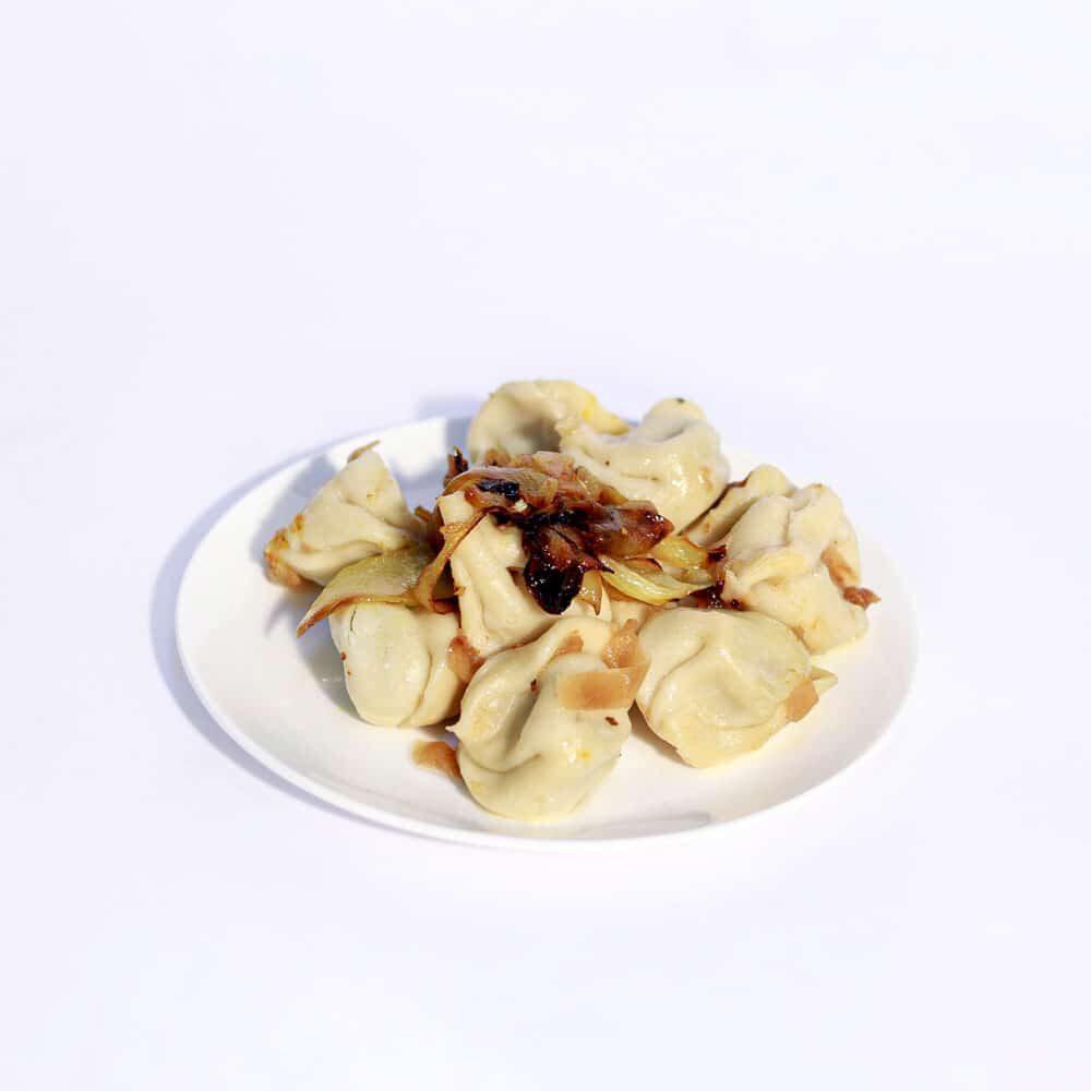 כיסוני בצק ממולא בבשר מעוטר בבצל מטוגן